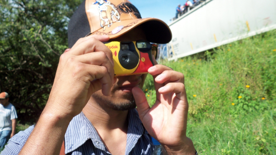 A MigraZoom participant, a young migrant, familiarizes himself with a disposable camera.
