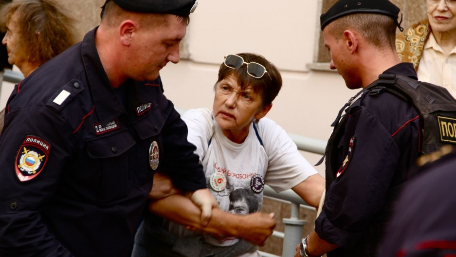 Outside the court on the day of Gaskarov's sentencing, a lone protester is hurried away by the police.