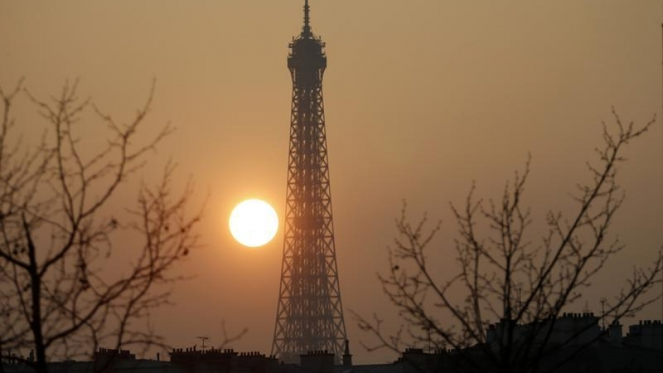 The sun sets through unusually smoggy skies behind the Eiffel tower on Friday, March 14. Swathes of France, including the French capital, were on maximum alert over air pollution, prompting Paris authorities to make green transportation such as its Velib