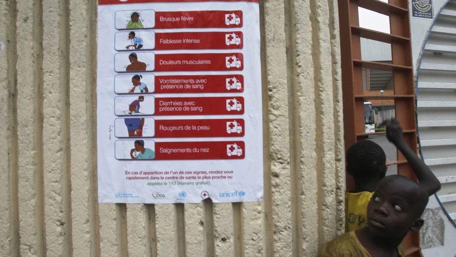 Boys stand next to a poster pertaining to the Ebola virus during a training session by Sierra Leone's national soccer team at the Felix Houphouet Boigny stadium in Abidjan on September 5, 2014.