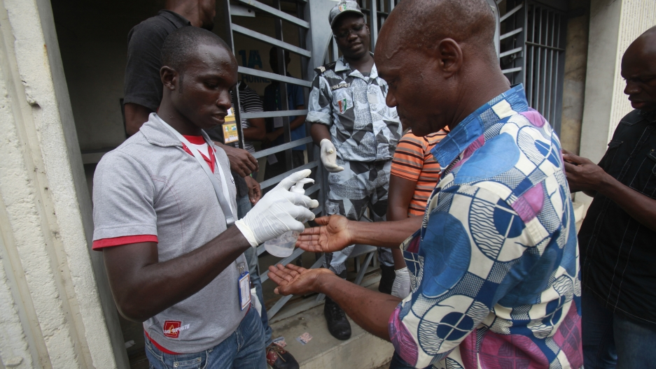 Fans of Ivory Coast clean their hands with antiseptic solution during the 2015 African Nations Cup qualifying soccer match between Ivory Coast and Sierra Leone at the Felix Houphouet Boigny stadium in Abidjan on September 6, 2014.