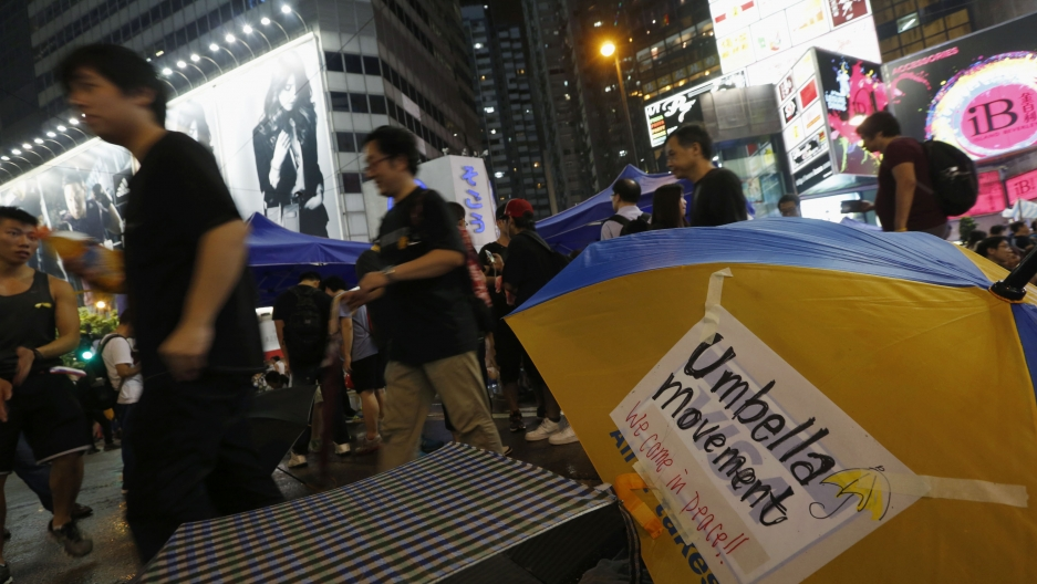 Protesters walk past an umbrella as they block the main road at Causeway Bay shopping district. Tens of thousands of pro-democracy protesters extended a blockade of Hong Kong streets on Tuesday, stockpiling supplies and erecting makeshift barricades. As t