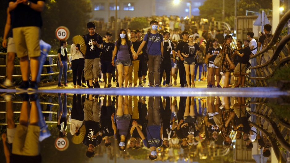 Protesters walk along a street as they block an area near the government headquarters building in Hong Kong.