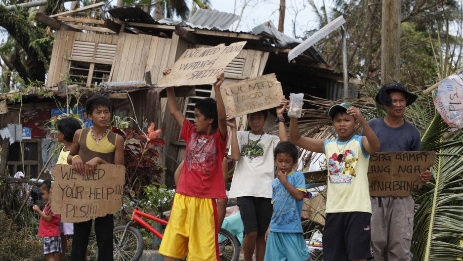Children hold signs asking for help and food along the highway, after Typhoon Haiyan hit Tabogon town in Cebu Province