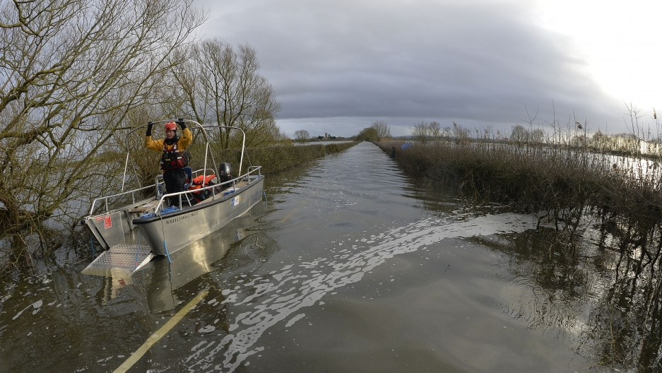 A boat operated by emergency services personnel waits to be driven down a flooded road to the village of Muchelney, seen in the background on the flooded Somerset Levels, near Langport in south west England January 27, 2014. Surrounded by flood water, Muc