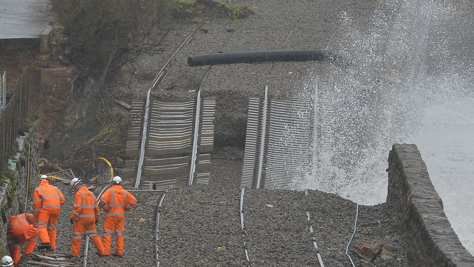Rail emergency workers inspect damaged tracks along the seafront at Dawlish in south-west England February 6, 2014. Storms destroyed sections of the mainline route to the south-west of England, and severe weather warnings for rain and gale force winds hav