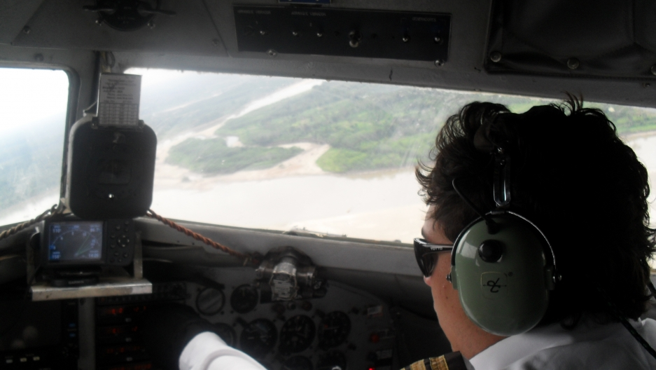 The co pilot looks out the DC-3 window at a jungle river. You can see the compass held in place by bungee cords.