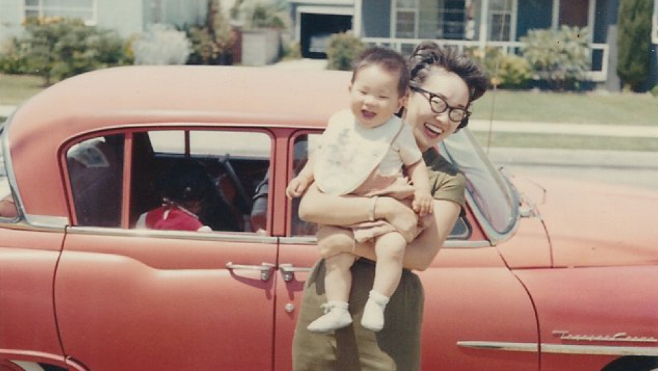 Bruce Kaji's wife holding their son, Troy, in front of the family car, the Red Toyota Toyopet, circa 1961. Bruce bought the car in 1958 from Hollywood Toyota.