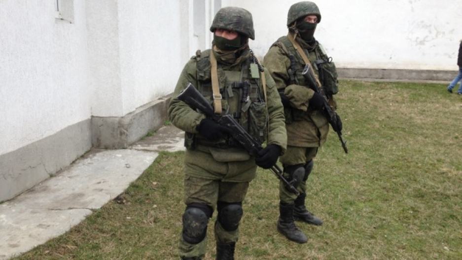 Two soldiers outside a military base in Crimea. They're heavily armed but their uniforms aren't marked. They refuse to say who they are and who they're protecting.