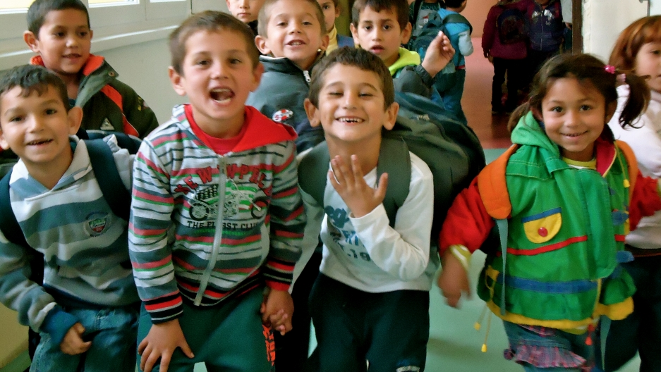 A group of young Roma students goof off in the hallway of Šarišské Michaľany elementary school.