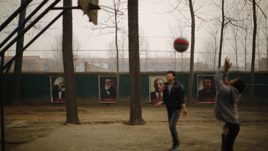 Students play basketball in the courtyard of the Democracy School, with Marx, Engels, Lenin and Stalin looking on.