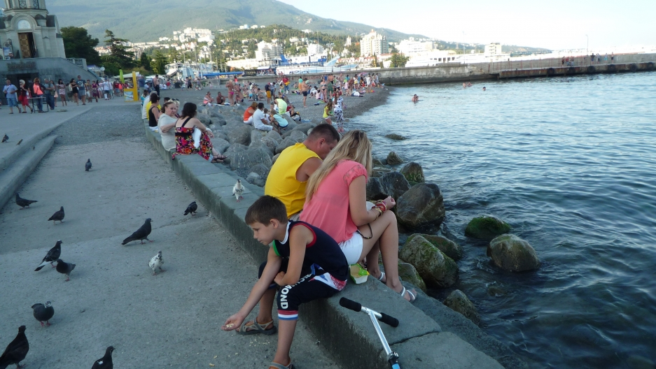 Boy feeds pigeons along the Yalta waterfront.