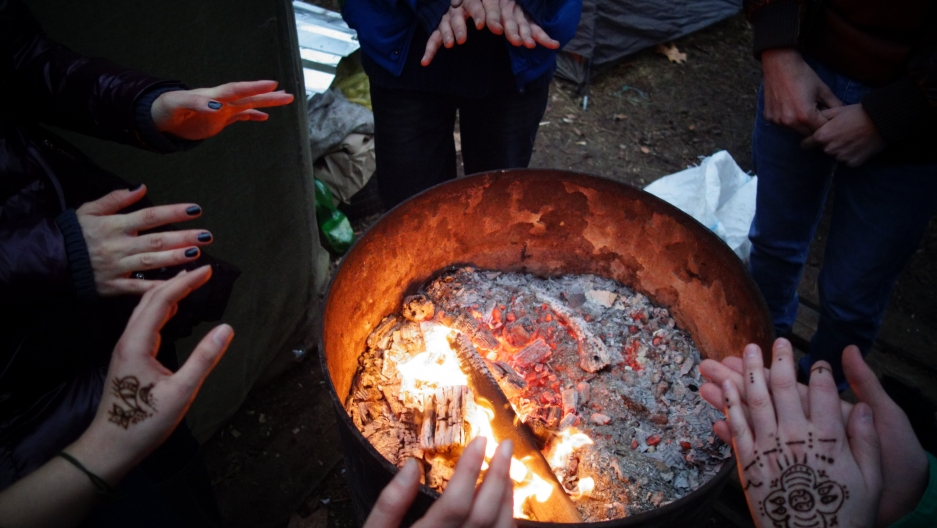 "Tbilisi's ""Guerrilla Gardening"" movement formed their camp on January 24, the coldest month of the year. Friends warm their hands over a burn barrel to keep away the winter chill."