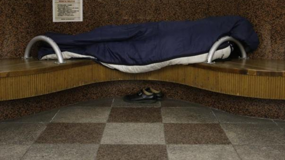 A homeless man snuggles in a sleeping bag on a bench at an underground passage near Sendai Station in Sendai, northern Japan, December 17, 2013.