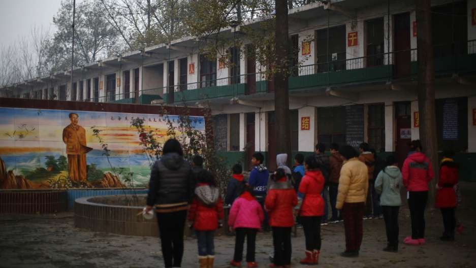 Students at Xia's Democracy School in rural Henan province pay respect at a mural of Mao Zedong.
