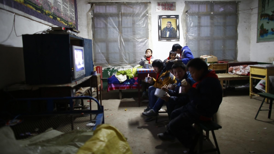 Students watch television while eating. Their viewing choices include historical movies with nationalist themes.
