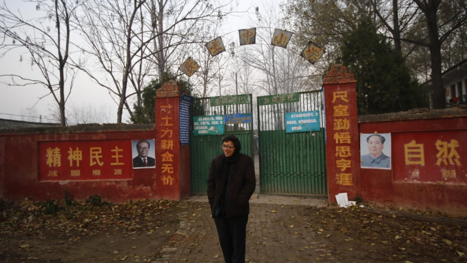 Principal Xia Zuhai stands in front of the Democracy School he founded in Henan province. The curriculum is infused with Mao Zedong Thought.