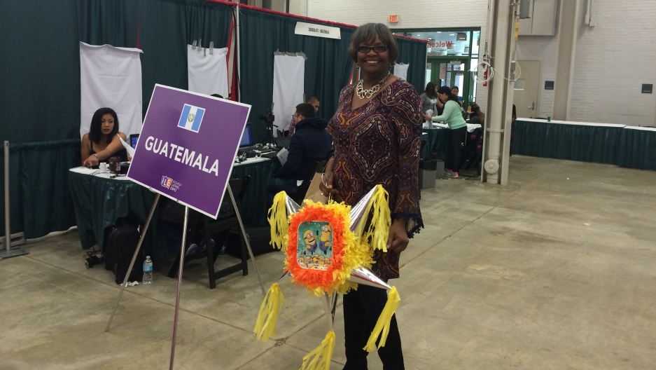 "A woman stands in conference area in front of ""Guatemala"" sign"