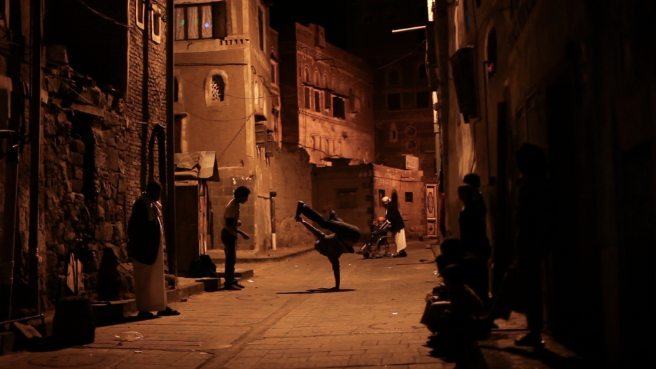 "A break dancer strikes a pose in the streets of Sanaa, Yemen, in a scene from the new documentary, ""Shake the Dust."""