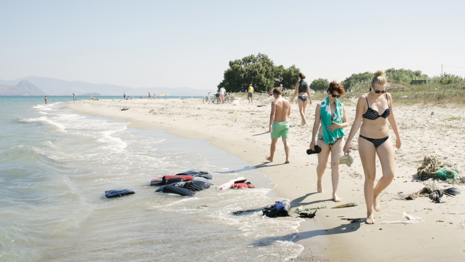 Tourists walk past life preservers on the beaches of Kos, Greece.