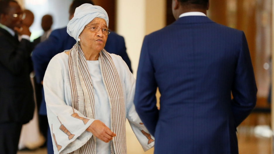 Ellen Sirleaf wears a grey headwrap and robe as she speaks to a man in a blue suit.