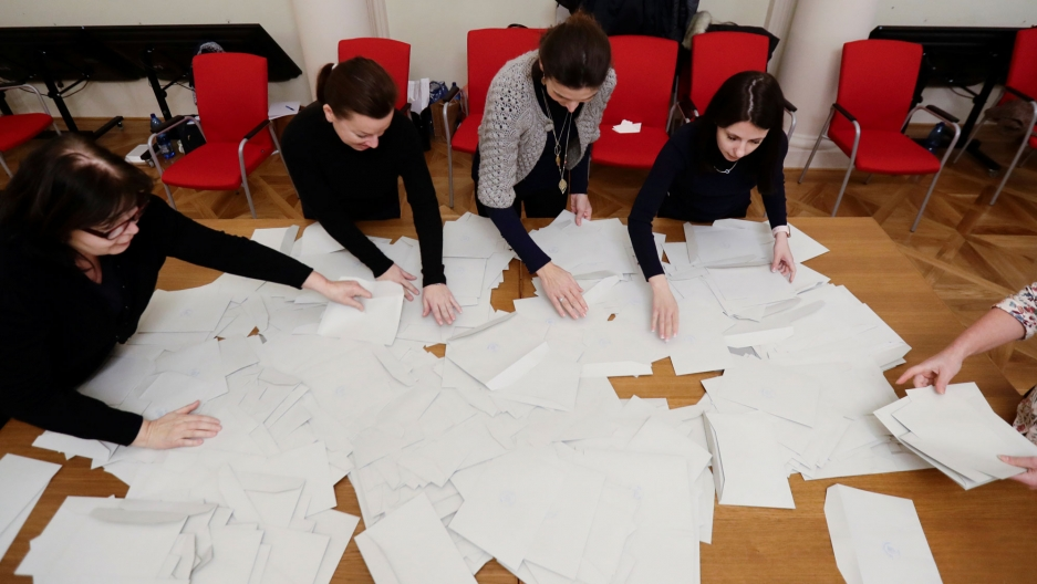Four people sit at a table covered in white papers, which are ballots, with their hands outstretched as they sort through the pile