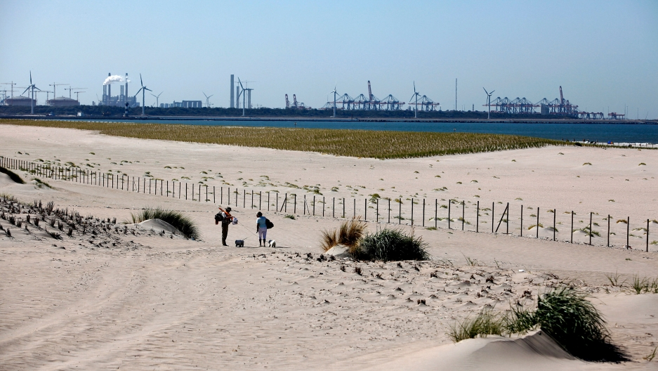 Two people walk across the beach sand. Across the water are wind turbines and other buildings