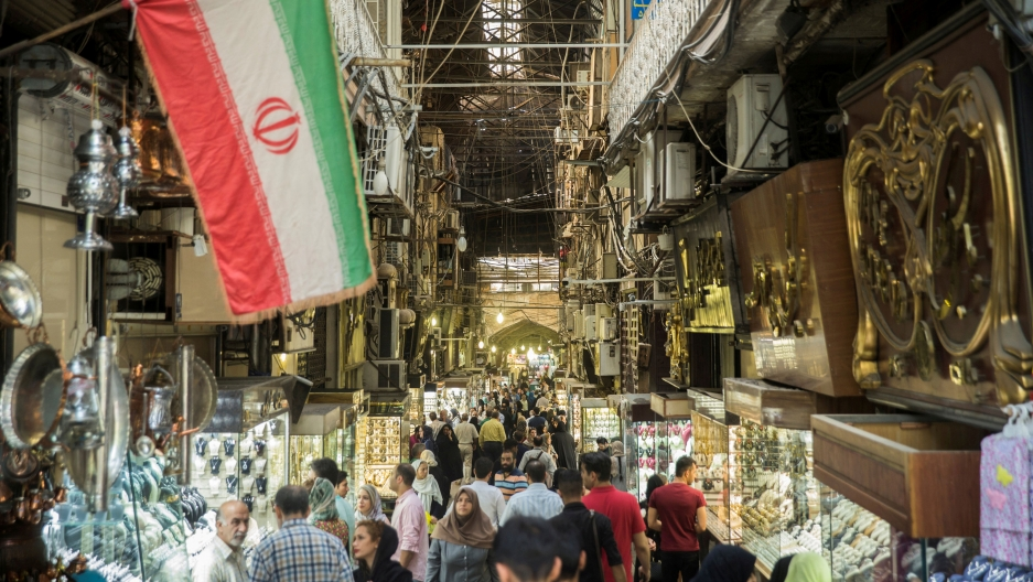 Crowds fill the bottom of the frame. On both sides are shops and the on the right side of the image is an Iranian flag