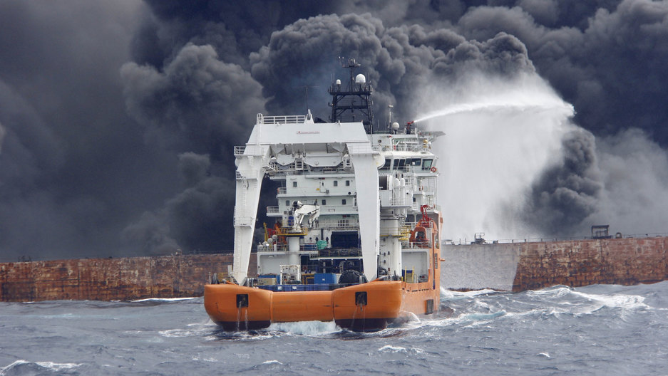 A smaller boat shoots a jet of water out a dark, billowing clouds of smoke coming from a brown metal tanker ship