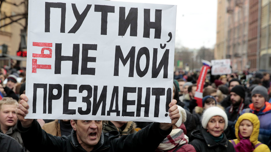 "A man holds a white sign with lettering in Russian. He is surrounded by dozens of others. The sign says ""Putin, you are not my president."""