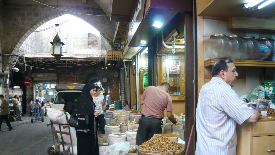 Several people look at bags of dried ingredients laid outside a shop. In the foreground, a man leans against a stall.