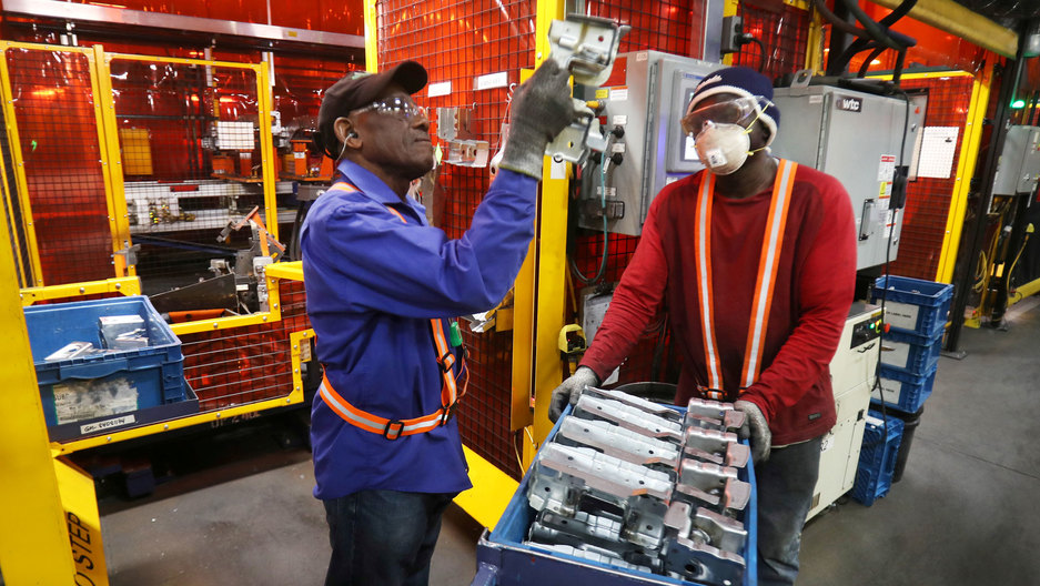 One person inspects a piece of metal, while another person holds a cart containing a more of the same pieces of metal.