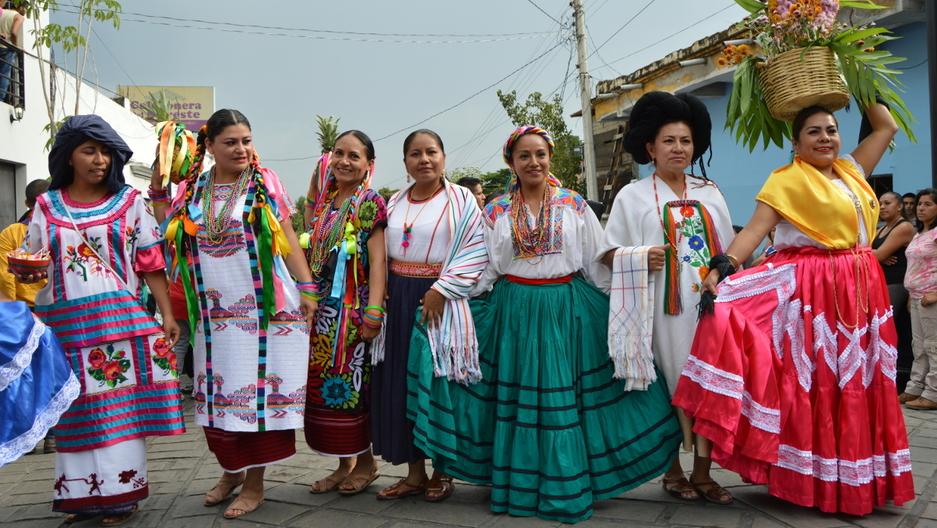 Teachers pose in traditional regional dress from some of Oaxaca's eight regions
