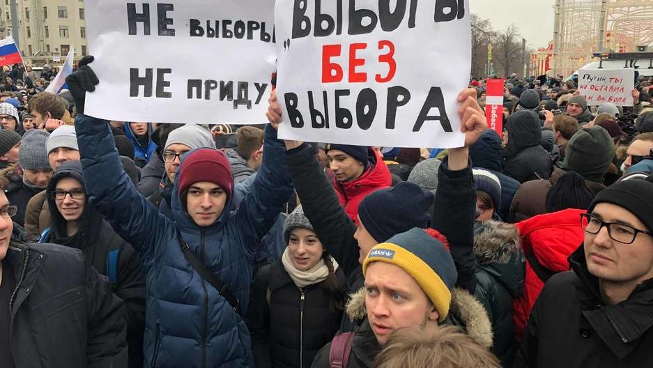 A crowd of young people are gathered. Two hold up two large signs in Russian.