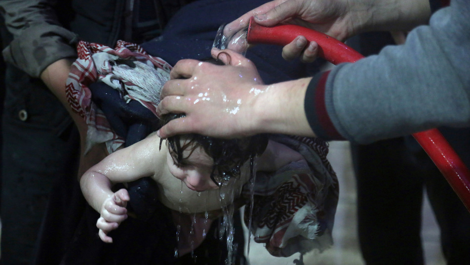 Hands hold a hose over a child's head and water streams down his hair and face.