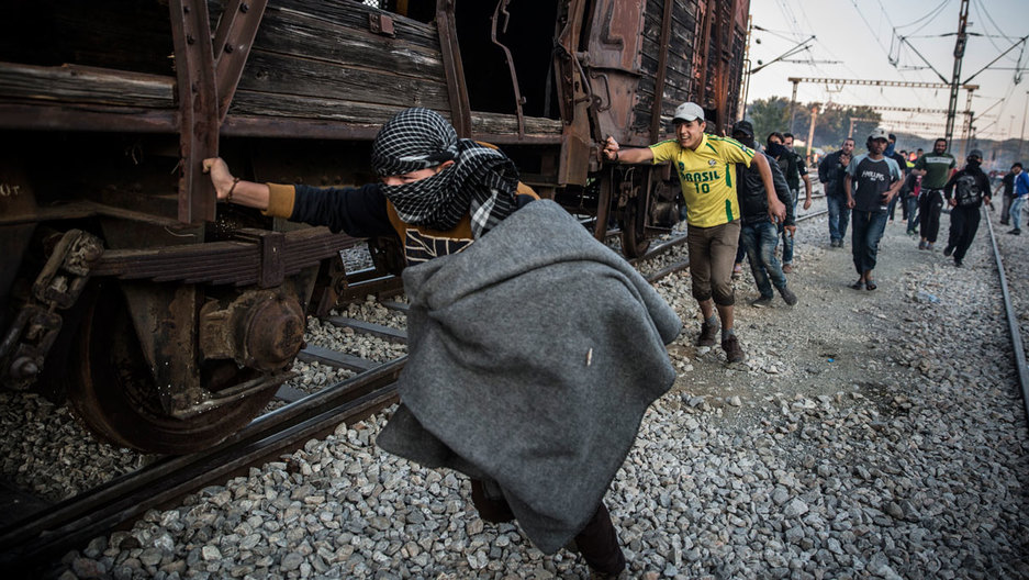 Protesting migrants pushed an abandoned train wagon toward the border during a protest on May 18, 2016, at Idomeni camp. Clashes ensued between Greek police, who fired tear gas and stun grenades and immigrants.
