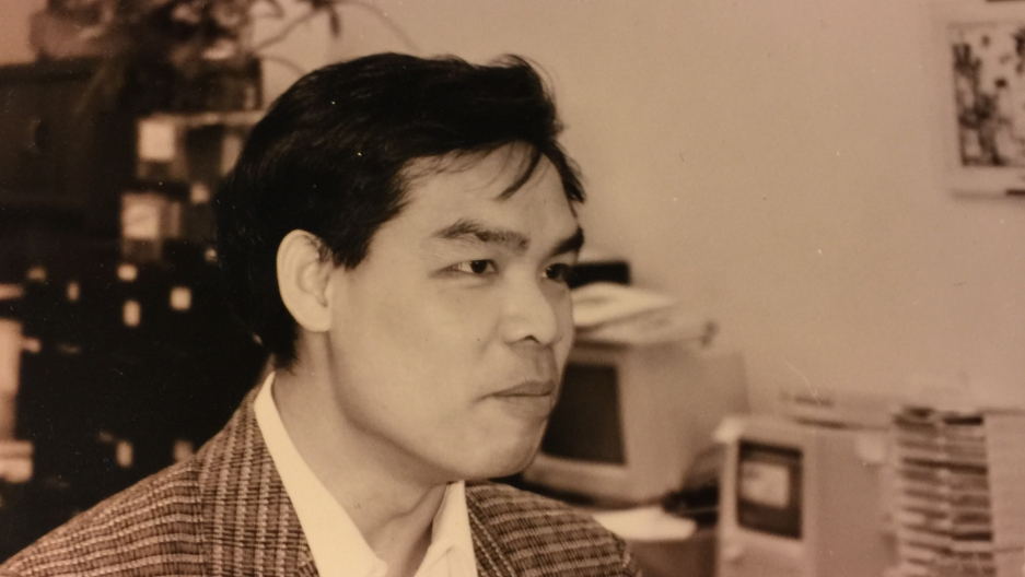 Sepia-tone image of man in jacket, profile photo, in front of 1980s computers
