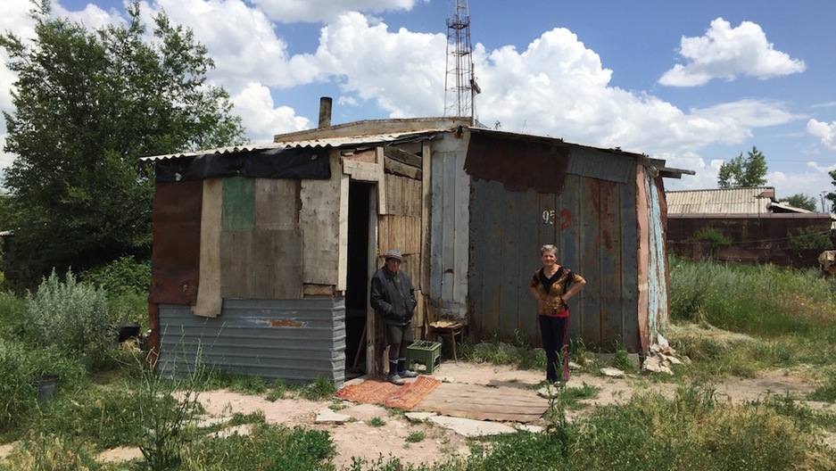 Armenian sisters Arev, left, and Lida stand in front of their home built from a shipping container.