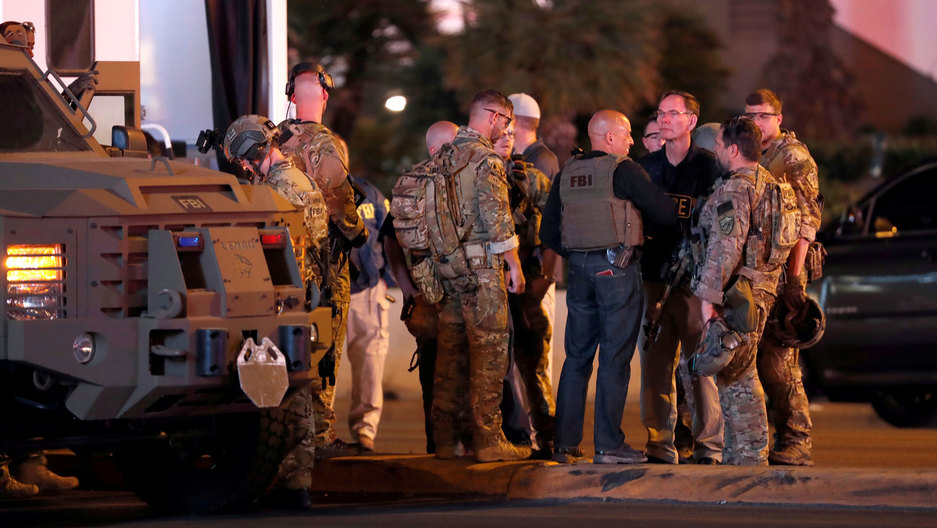 A group of men wearing camouflage clothing and FBI vests stand next to an armored car outside the Mandalay Bay Hotel in the pre-dawn light.