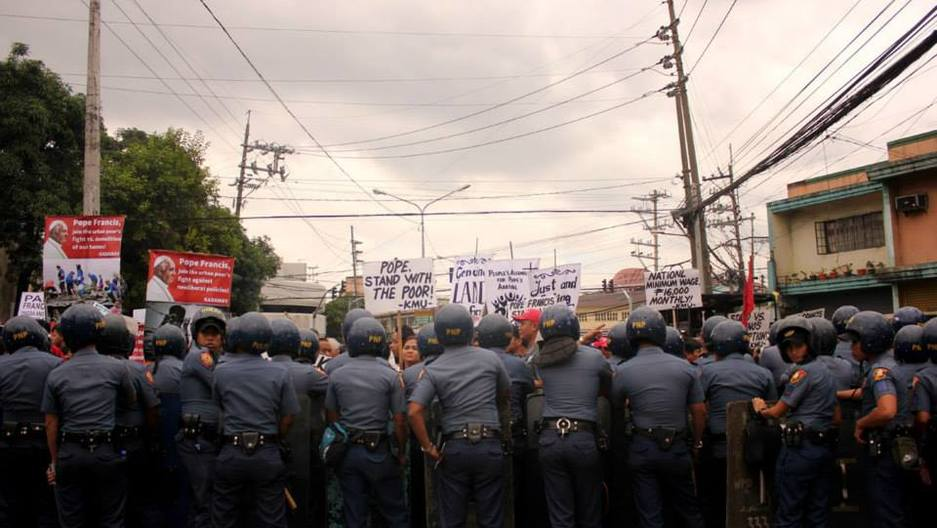 Phillipine police block protesters from marching within sight of Pope Francis' motorcade in Manila on January 15, 2015.