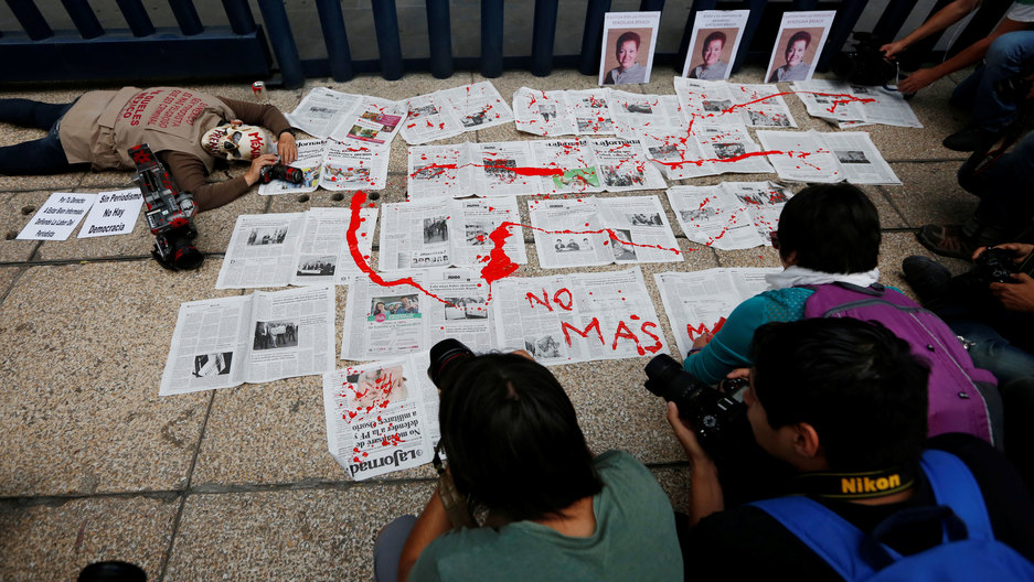 """Photographers are huddled around a protest on the sidewalk. There are newspapers laid out on the sidewalk, drizzled in red paint to look like blood, while a person wearing a skull mask pretends to lay dead next to them. The words """"No mas"""" are written."""