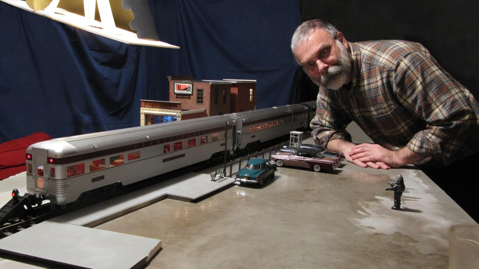 Model-maker Michael Paul Smith poses with a model of a passenger train.