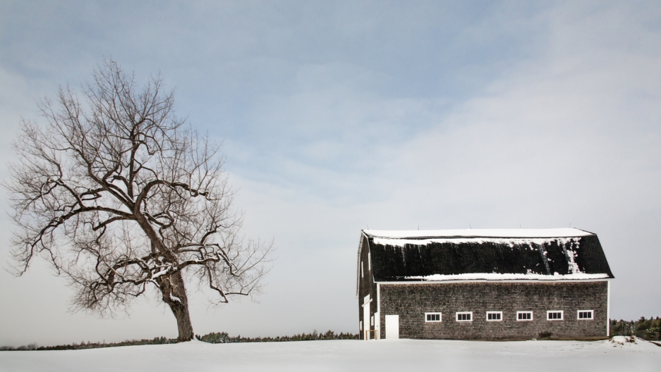 Winter scene of a barn covered in snow