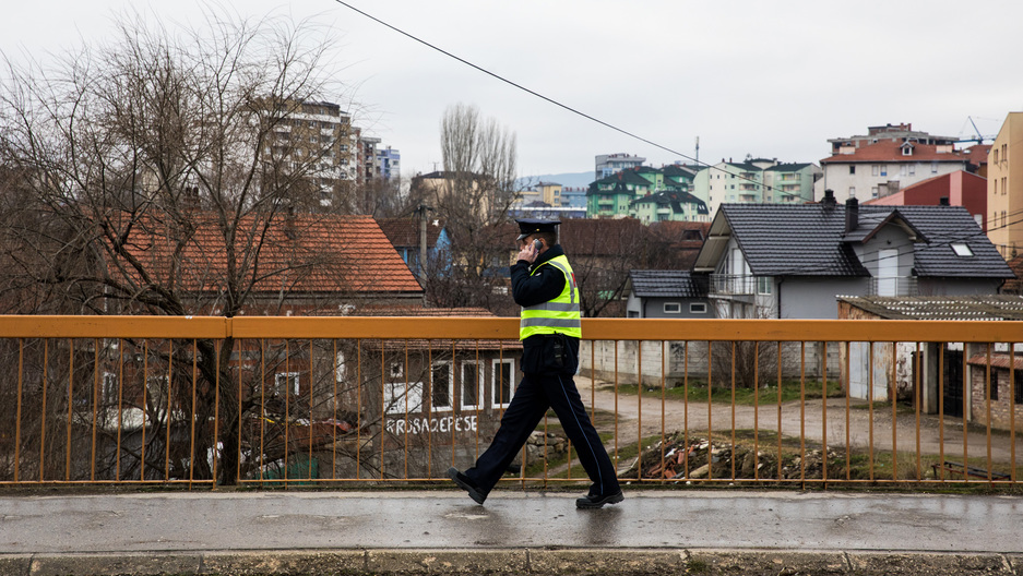 A Kosovo police officer crosses the bridge that connects north and south Mitrovica. The Ibar River serves as a natural divider in Mitrovica, where Serbs live on the northern side of the river and Albanians on the southern side.