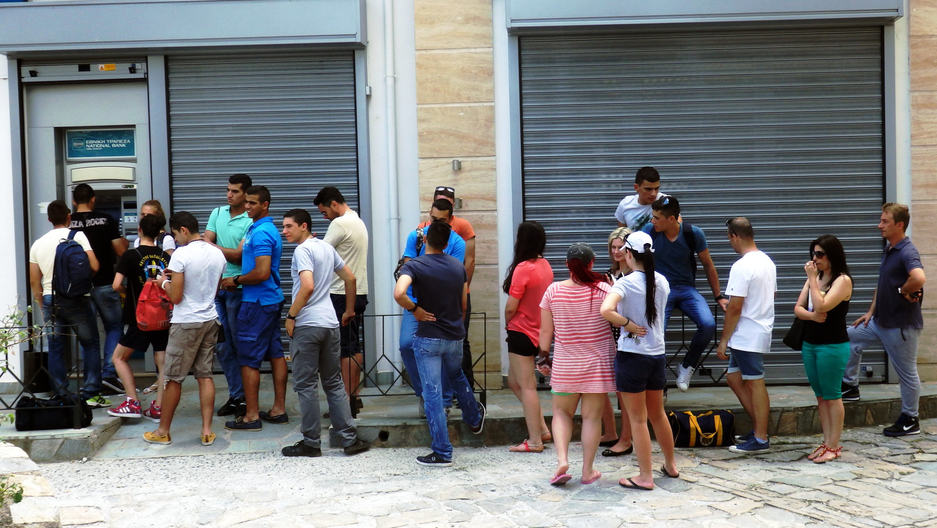 People lined up outside of an ATM in Greece.