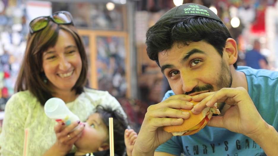 A French tourist eats a kosher McDonalds hamburger with a potato-starch bun in downtown Jerusalem.