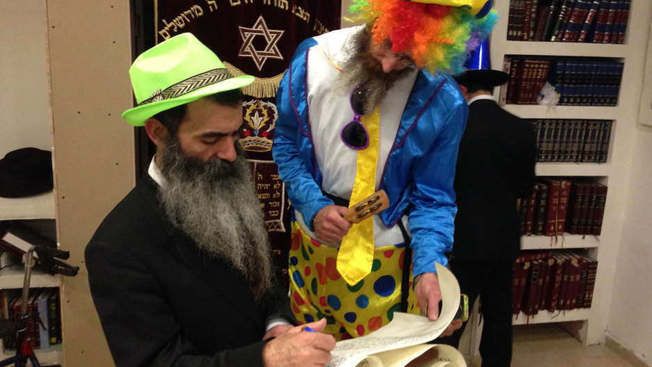 Orthodox Jewish men in costume read from a scroll of the biblical Book of Esther for the Jewish carnival holiday of Purim. The story tells the tale of an ancient Persian king whose viceroy hatches a plot to kill the Jews of the kingdom, a plot that is thw