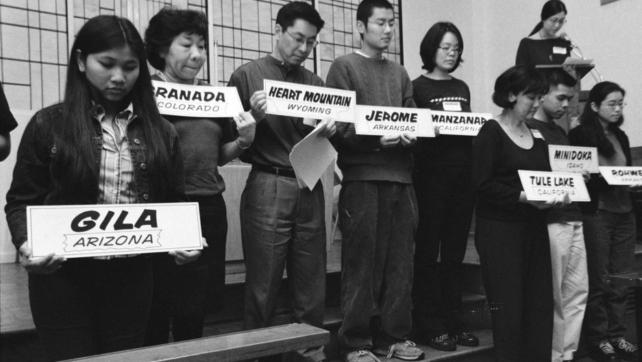 black and white photo of people holding up signs of location names