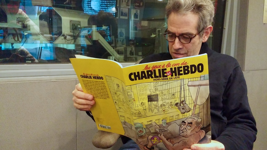 Marco Werman reads an issue of French satirical newspaper Charlie Hebdo he bought during a trip to France in 2011.