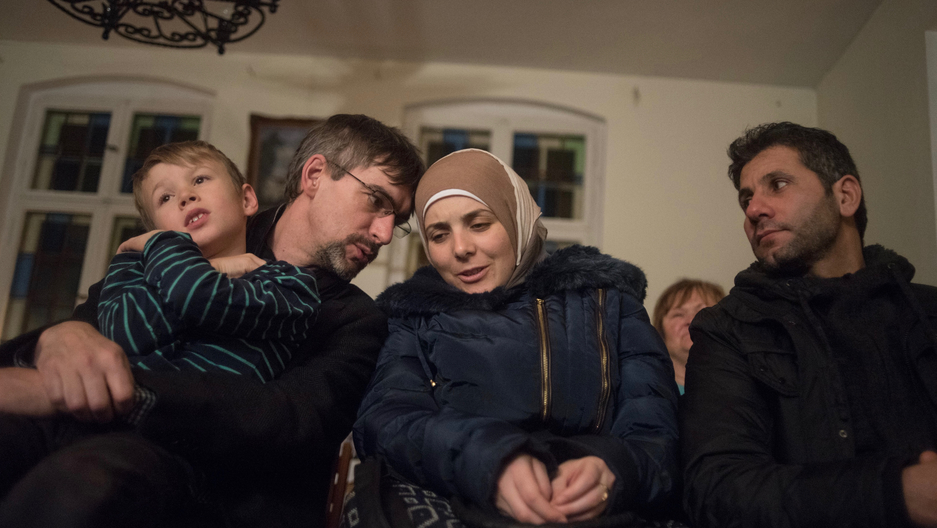 Golzow mayor Frank Schütz, left, leans over to whisper a question to Rasha Haimoud during a holiday concert. She and her husband, Ahmad Haimoud, are refugees who settled in the small former East German town after escaping the war in their native Syria